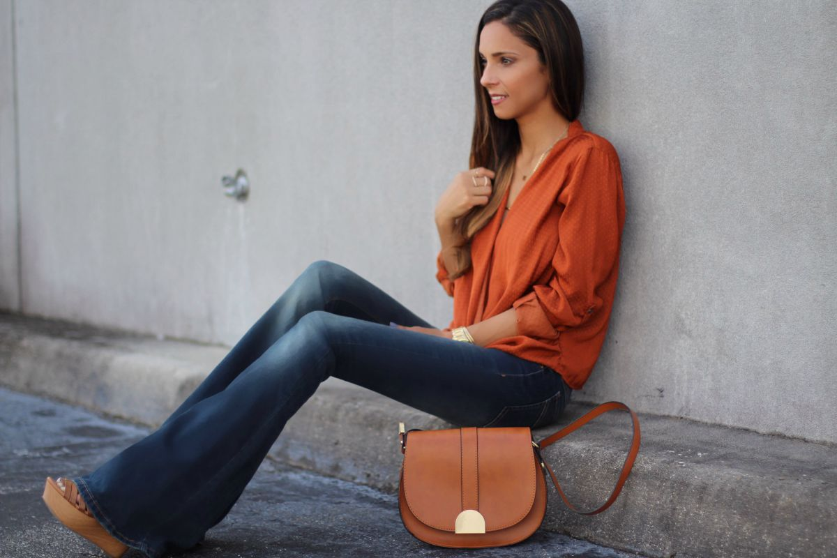 Free People stretchy flare jeans, a rust wrap blouse and wedges