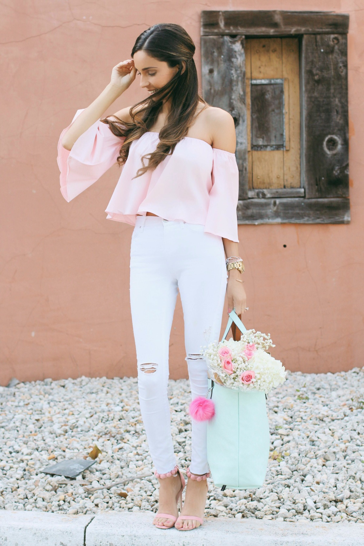 Thalia pink off the shoulder crop top with white ripped jeans and mint vegan leather bag