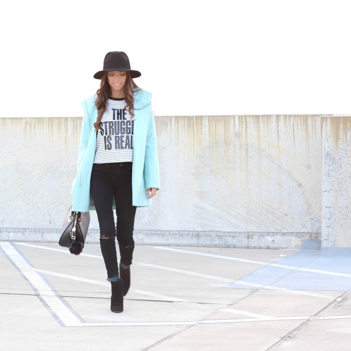 The Struggle is Real graphic tee with aqua coat, black jeans, booties and fedora